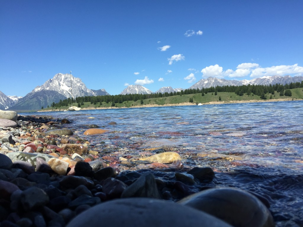 Beautiful view of Jackson Lake in Grand Teton National Park and the stones in the water with the mountains in the background.