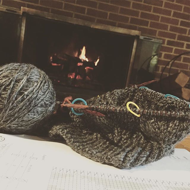 Photo of a hat partially knitted with a fire in the background.